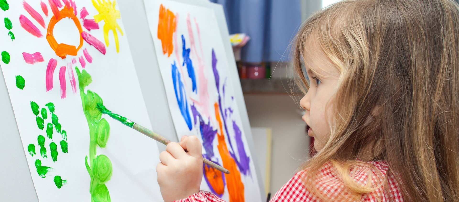 Cute little blond girl holding brush and painting on paper